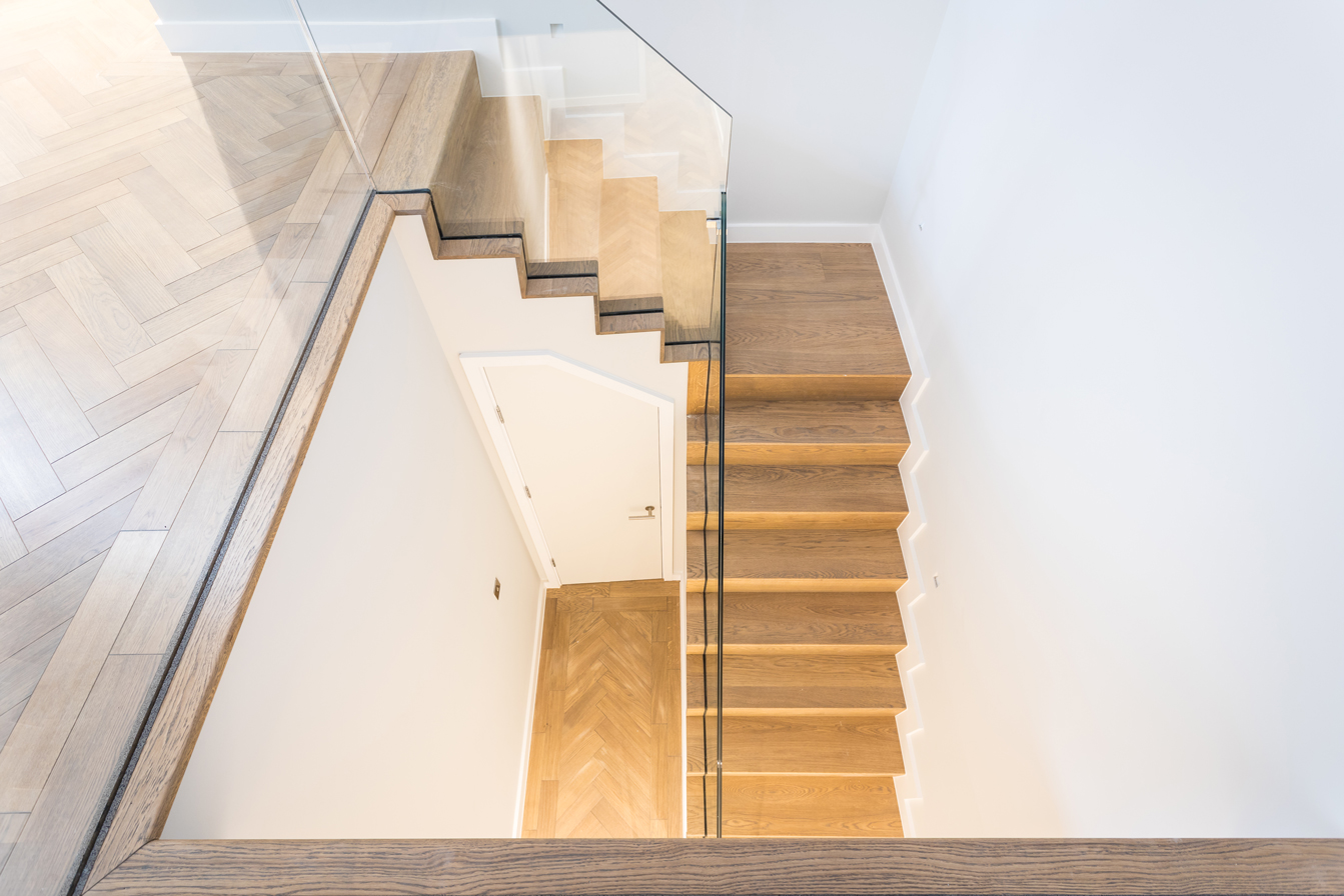 wooden staircase with glass panel bannister