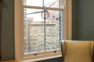 window looking out to small garden with brick wall