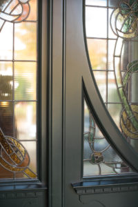 artisan woodwork on black door with stained glass windows