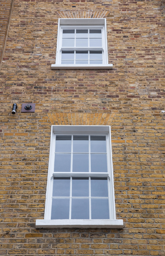 two windows on brick wall