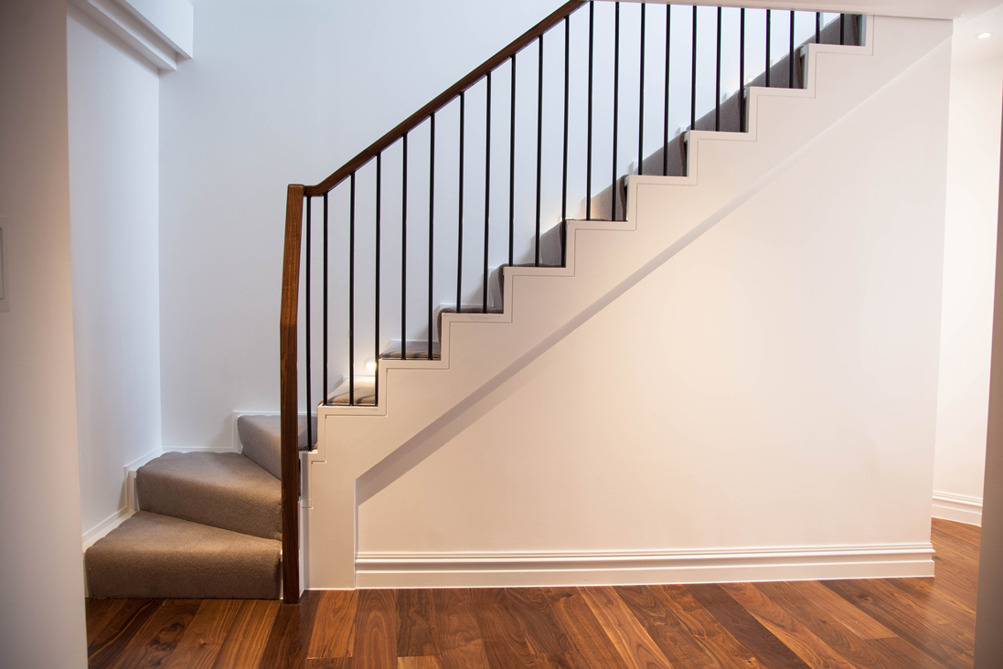 modern wooden staircase with metal plank bannister