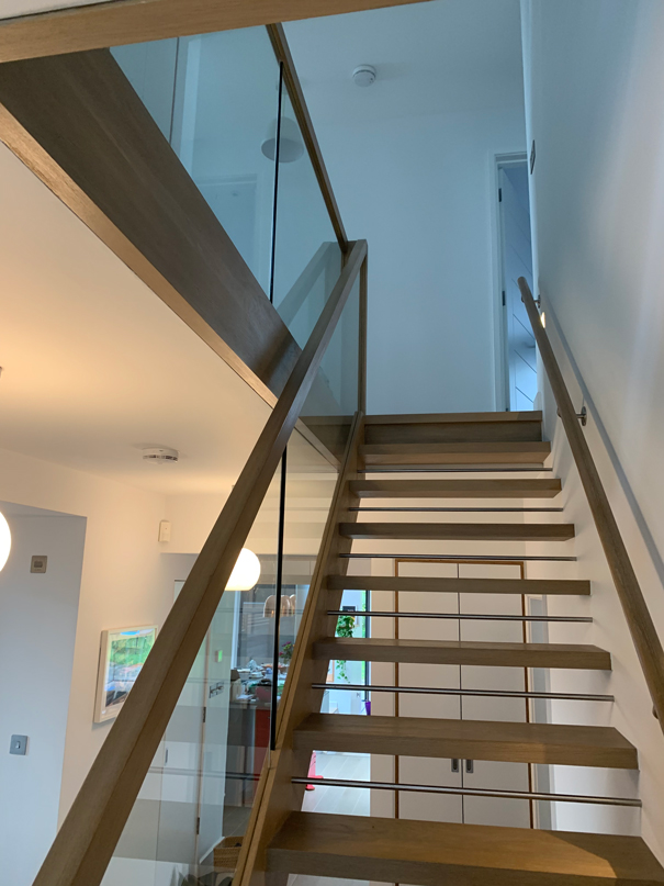 wooden staircase with glass window bannister