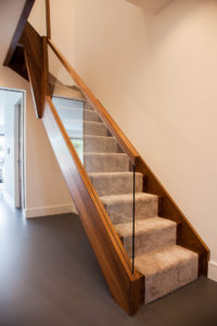 wooden staircase with glass panel window and handrail