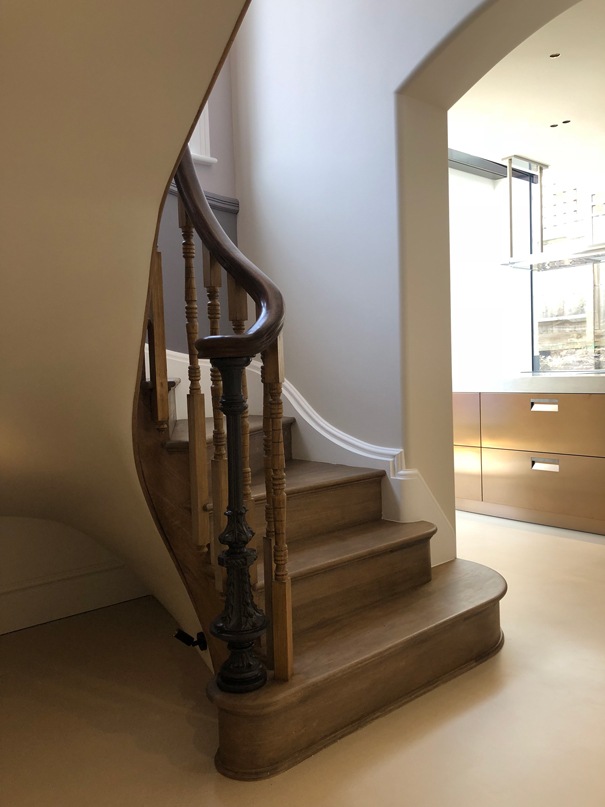 spiral wooden staircase with bannister , dark wood