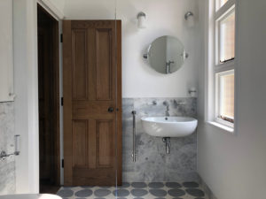modern bathroom with marble wall and wooden door