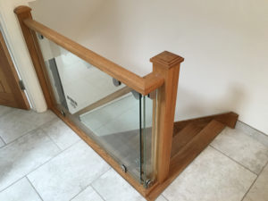 wooden hand rail bannister with glass pannels