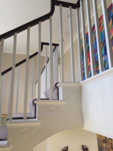 white open staircase with landing and black banister