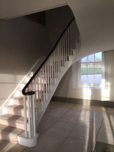 white open staircase with landing and black bannister