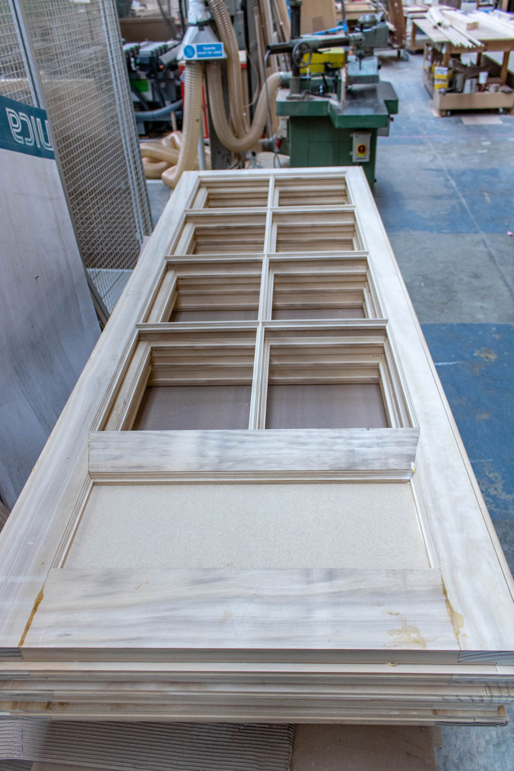 stack of thin 8 panel wooden doors in joinery workshop