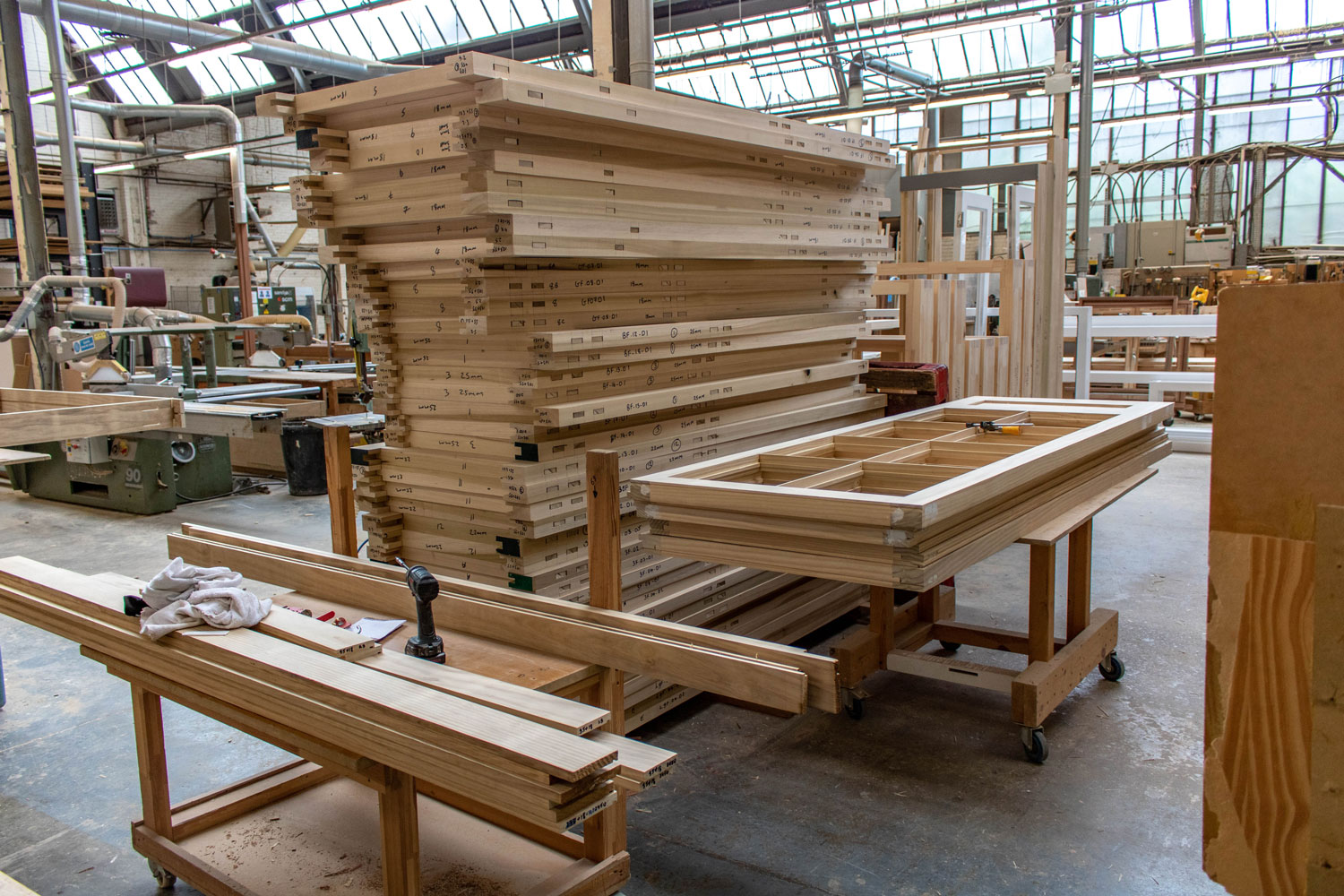 large stack of wooden window frames in joinery workshop