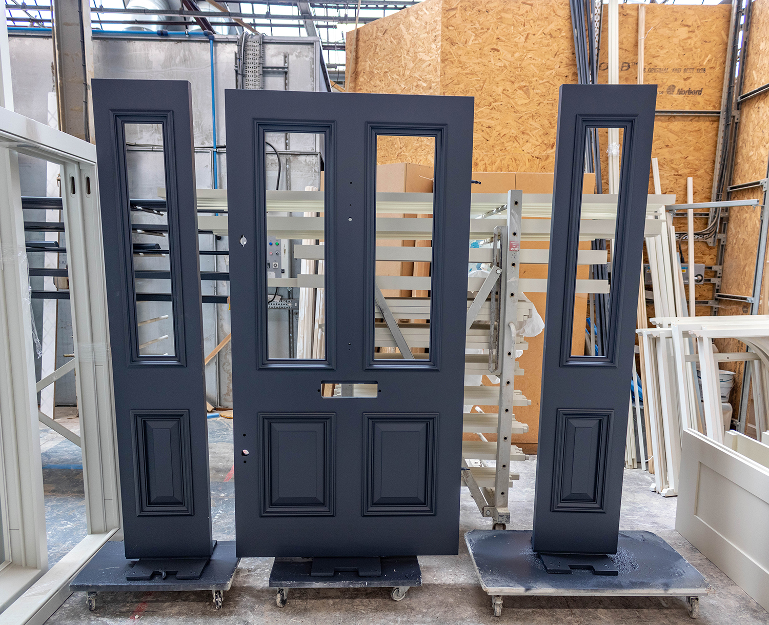 grey set of front door and two side panels in joinery workshop