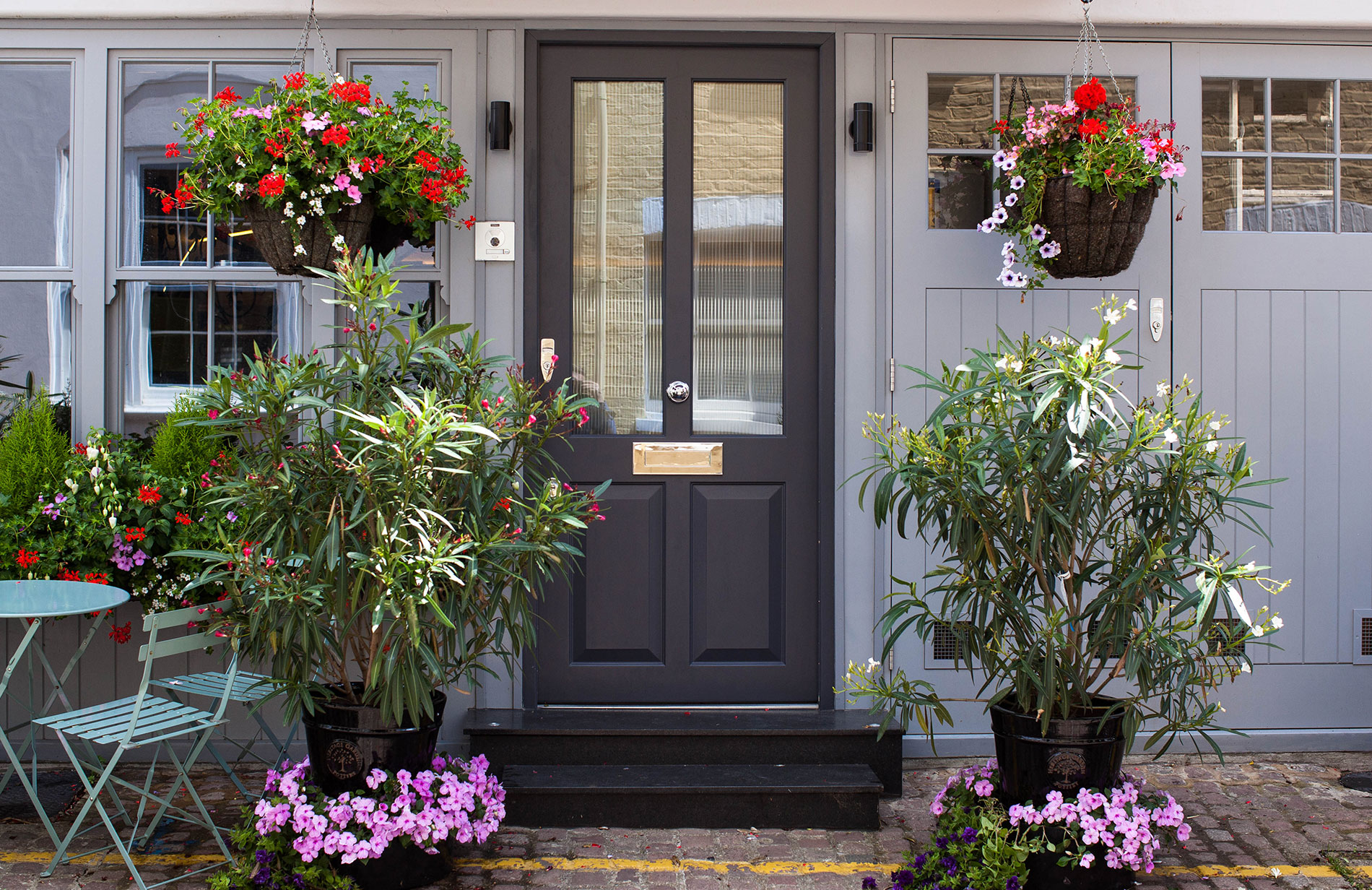 modern black front door with plants and greenery